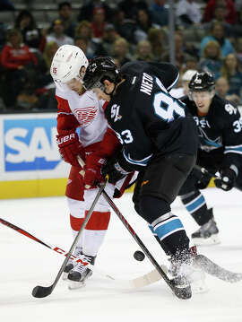 The Sharks' Matt Nieto battles for control of the puck with Detroit's Riley Sheahan.