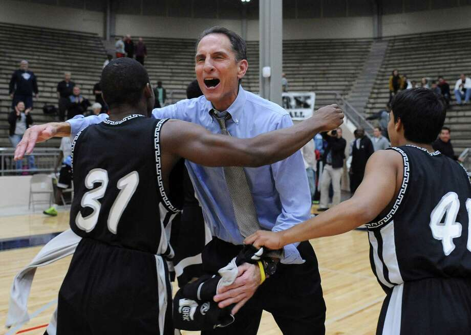 Clark coach Steve Sylestine celebrates with players William Young (31) and Johnatan Reyes after the Cougars defeated Reagan in a Class 6A second-round playoff game at the Alamo Convocation Center. Photo: Billy Calzada /San Antonio Express-News / San Antonio Express-News