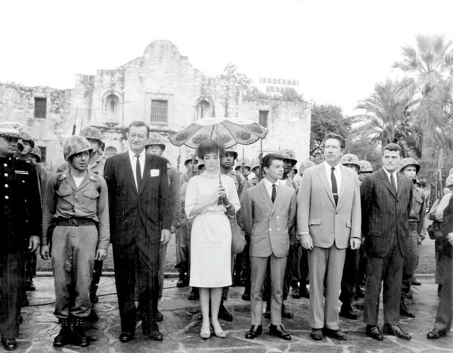 """Cast members of the 1960 film """"The Alamo,"""" including (from left of the helmeted soldier) John Wayne, Linda Cristal, Frankie Avalon, Richard Boone and Pat Wayne, pay tribute to the fallen defenders of the Alamo during a ceremony on Alamo Plaza on Oct. 24, 1960, the morning of the world premiere of the film. (Express-News Archives) Photo: EXPRESS-NEWS FILE PHOTO"""