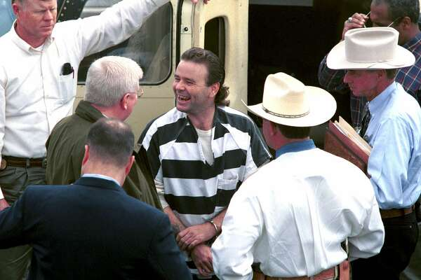 Tommy Lynn Sells, center, laughs with law enforcement officers after getting off a plane at Central Flying Service in Little Rock, Ark., Wednesday, March 22, 2000. Sells was brought to Little Rock by Texas Rangers to talk to authorities about two murders he claims to have committed in Little Rock. The killings are among 13 that Tommy Lynn Sells says he carried out in seven states. But Texas authorities have said they are less sure about the accuracy of Sells' Arkansas claims than about some of the other slayings.