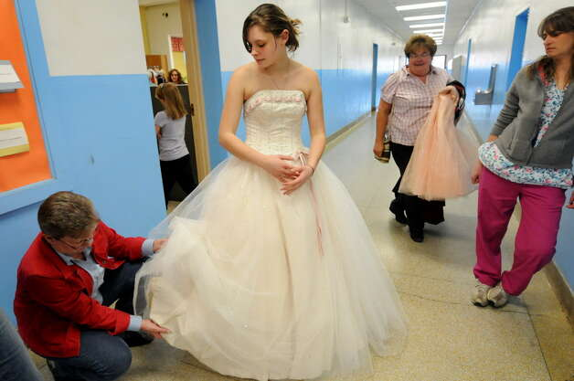 Ashley Woolley, 17, center, tries on a donated prom dress as Kathy Beers of Glenville checks it for alterations on Friday, March 30, 2012, at Schoharie High in Schoharie, N.Y. More than 300 dresses were collected to help make prom possible for the flood-stricken town. A similar program will be offered at the NY Women?s Expo on Saturday, Feb. 28, and Sunday, March 1, at Siena College. Dresses are $9.95 and proceeds benefit Big Brothers Big Sisters of the Capital Region. Find information at http://nywomensexpo.com/.  (Cindy Schultz / Times Union) Photo: Cindy Schultz / 00017037A