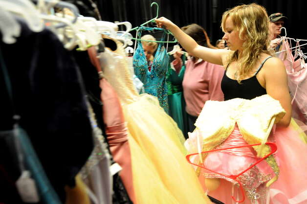 Hailey Upton, 18, looks through racks of prom dresses on Friday, March 30, 2012, at Schoharie High in Schoharie, N.Y. More than 300 dresses were collected to help make prom possible for the flood-stricken town. A similar program will be offered at the NY Women?s Expo on Saturday, Feb. 28, and Sunday, March 1, at Siena College. Dresses are $9.95 and proceeds benefit Big Brothers Big Sisters of the Capital Region. Find information at http://nywomensexpo.com/.  (Cindy Schultz / Times Union) Photo: Cindy Schultz / 00017037A