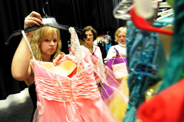 Hailey Upton, 18, left, looks over a prom dress on Friday, March 30, 2012, at Schoharie High in Schoharie, N.Y.  More than 300 dresses were collected to help make prom possible for the flood-stricken town. A similar program will be offered at the NY Women?s Expo on Saturday, Feb. 28, and Sunday, March 1, at Siena College. Dresses are $9.95 and proceeds benefit Big Brothers Big Sisters of the Capital Region. Find information at http://nywomensexpo.com/.  (Cindy Schultz / Times Union) Photo: Cindy Schultz / 00017037A