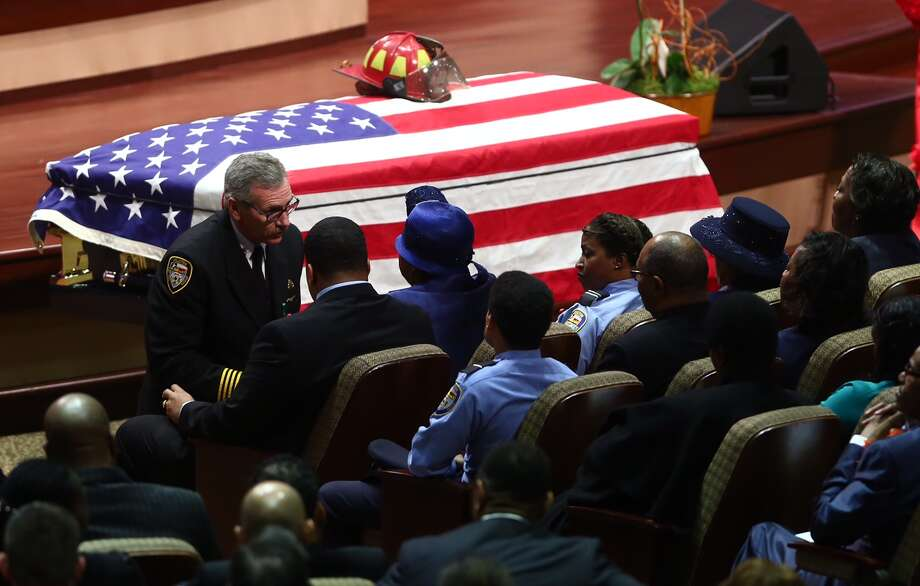 HFD Fire Chief Terry Garrison shares a moment with the family of Capt. Dwight Bazile during his memorial service at the Church Without Walls on Feb. 27, 2015. Photo: Marie D. De Jesús/Houston Chronicle