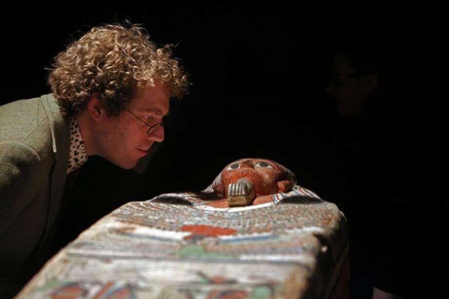 Curator Tom Hardwick inspects a 2,500-year-old coffin going on display at the Houston Museum of Natural Science. The white backgrounds and simple drawings are typical of mass produced coffins from the last thousand years of Pharaonic history. In the middle of the lid, the mummified dead person is shown lying on a lion-headed bier, his internal organs in canopic jars underneath him. Photo: Mayra Beltran, Houston Chronicle