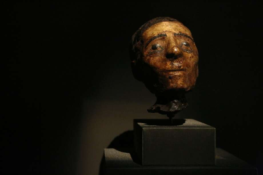 A head of a mummy, linen, pigment, gold leaf from 200 BC - 100 AD on exhibit in the Egyptian Hall at the Houston Museum of Natural Science.  Mummies from the Ptolemaic and Roman Periods are sometimes elaborately wrapped and painted. Here, gold leaf has been applied to the dead person's face to show him or her basking in the life-giving rays of the sun. The dead person's up rolled eyes may reflect the Greek notion of 'apotheosis', looking upwards to acknowledge the presence of a deity. Photo: Mayra Beltran, Houston Chronicle