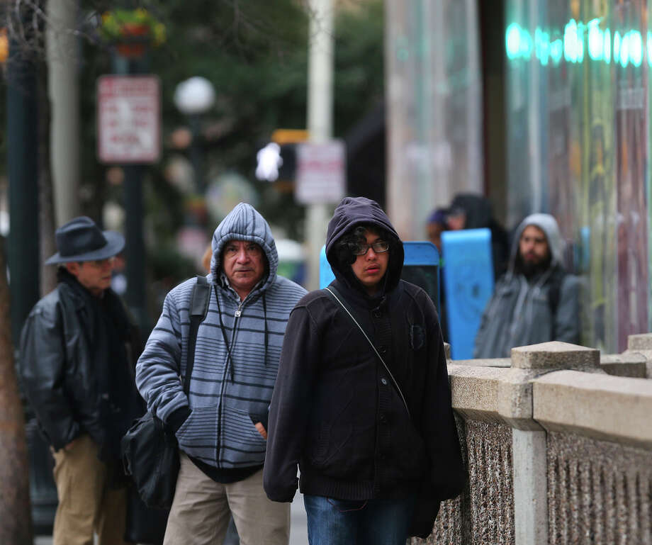 Pedestrians brave the cold temperatures Friday February 27, 2015 on St. Marys street in downtown San Antonio. Temperatures in the area have been in the 30 degree range. Photo: John Davenport, San Antonio Express-News / ©San Antonio Express-News/John Davenport