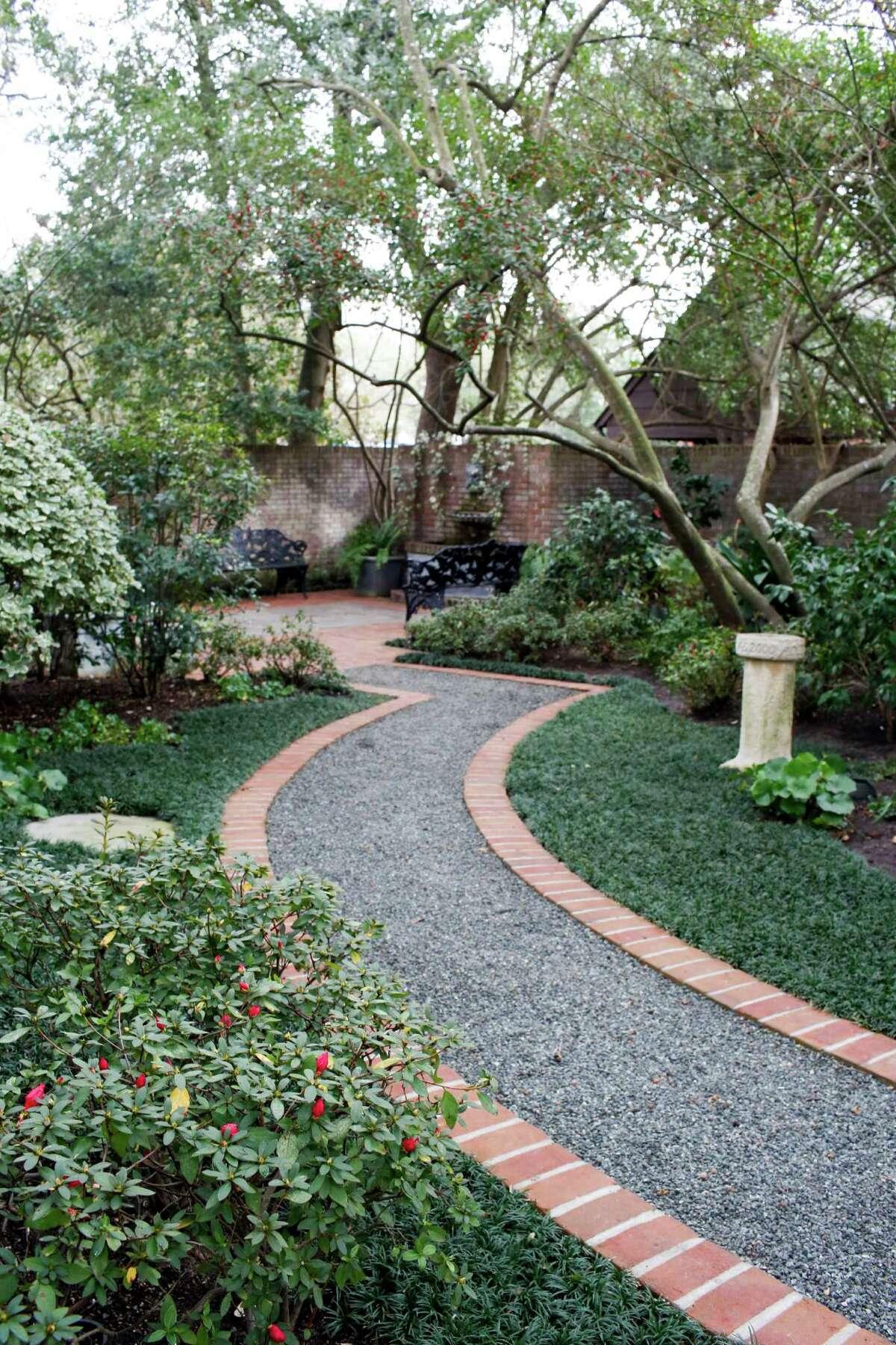 Varying green textures, camellias and azaleas line a garden path at a River Oaks home on the Azalea Trail.