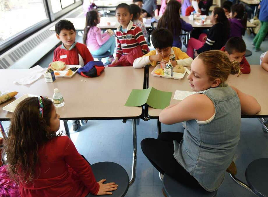 First-grader Yajaira Castro-Constanza, left, and fifth-grader Madison Tessar talk during a Diversity Day activity at New Lebanon School in Greenwich, Conn. Friday, Feb. 27, 2015.  The district's Embrace Diversity Day promoted acceptance among students in a number of activities including one in which students sat at a different lunch table moderated by a fifth grader to interact with kids they don't normally talk to at lunch. Photo: Tyler Sizemore / Greenwich Time