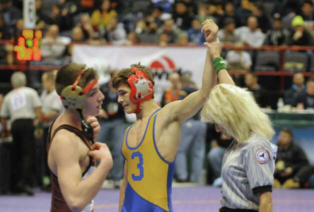 Albany Academy's Kyle Jasenski, left, lost his opening match in the 132lb. class to Dempsey King, center, from New Hartford during the opening rounds of the 2015 State Wrestling Tournament on Friday Feb. 27, 2015 in Albany, N.Y. (Michael P. Farrell/Times Union) Photo: Michael P. Farrell / 00030780A