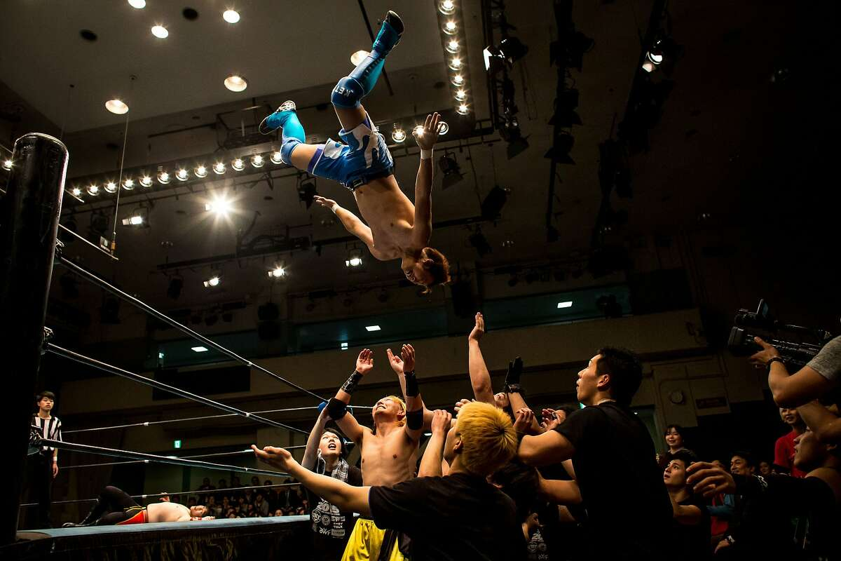 ACCORDING TO THE SCRIPT, WE'RE SUPPOSED TO CATCH HIM: A pro-style student wrestler launches himself on other wrestlers during a graduation fight night at Korakuen Hall in Tokyo. Japanese universities do not offer pro-style wrestling as a sport, so students form clubs and teach themselves moves and techniques primarily from YouTube videos.