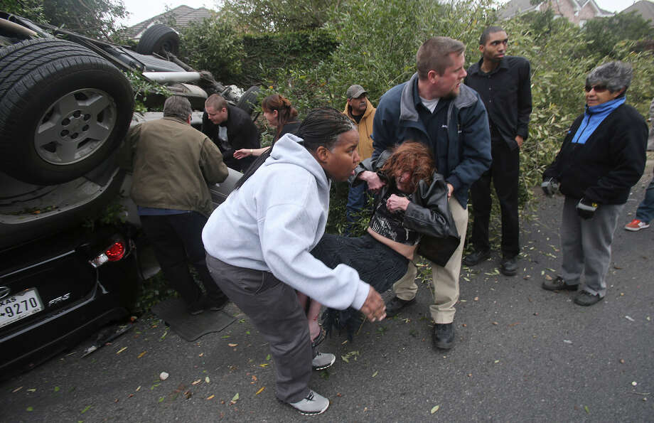 Raveta Johnson (left) and Matt Feeley (right) rescue an elderly woman Friday February 27, 2015 after the truck the elderly woman was in overturned and landed on top of a small sedan about 12:00 noon on the 800 block of East Basse road. Another man emerged from the truck and the driver of the car under the truck was not injured. Photo: John Davenport, San Antonio Express-News / ©San Antonio Express-News/John Davenport