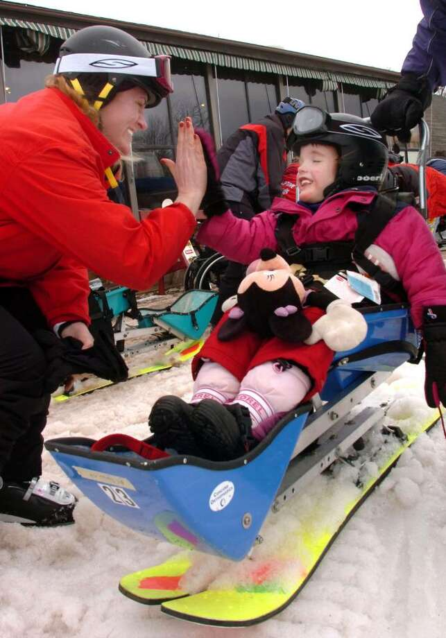 Vayle Nelson, 4, of Harlwinton, high fives her mom Susan Birk Nelson, 40, after finishing a run skiing on Mt. Southington during a Leaps Of Faith event on Wendesday, March 3,2010 Vayle has Ceberal Palsey and a big grin on his face. Photo: Michael Duffy / The News-Times