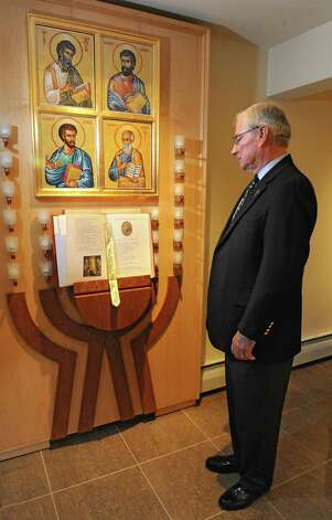 Deacon Dick Thiesen stands in front of a display with the book of gospels and images of Matthew. Mark, Luke and John in the newly renovated sanctuary at Christ Our Light Catholic Church on Wednesday, Feb. 25, 2015 in Loudonville, N.Y. Deacon Dick is the Parish Life Director at the church. (Lori Van Buren / Times Union) Photo: Lori Van Buren / 00030641A