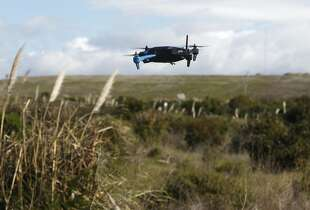 A drone hovers above a field in Brisbane, where a team of developers is creating the iDroneLink system, which would control and operate drones using iPhones and iPads.