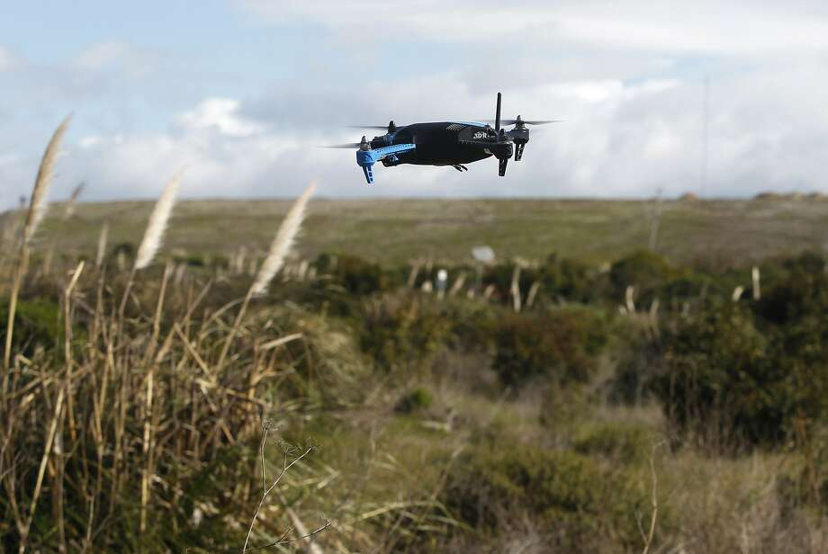 A drone hovers above a field in Brisbane, Calif. on Friday, Feb. 27, 2015. A team of developers have created the iDroneLink system, which controls and operates drones using an iPhone or iPad. Drone use is likely to skyrocket following new rules proposed by the FAA that are less restrictive than opponents were hoping for. Photo: Paul Chinn, The Chronicle