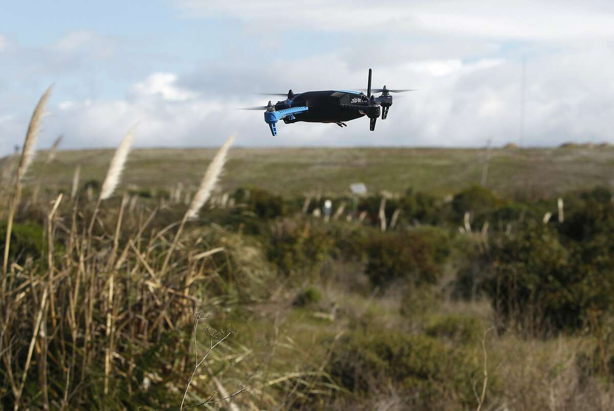 A drone hovers above a field in Brisbane, Calif. on Friday, Feb. 27, 2015. A team of developers have created the iDroneLink system, which controls and operates drones using an iPhone or iPad. Drone use is likely to skyrocket following new rules proposed by the FAA that are less restrictive than opponents were hoping for.