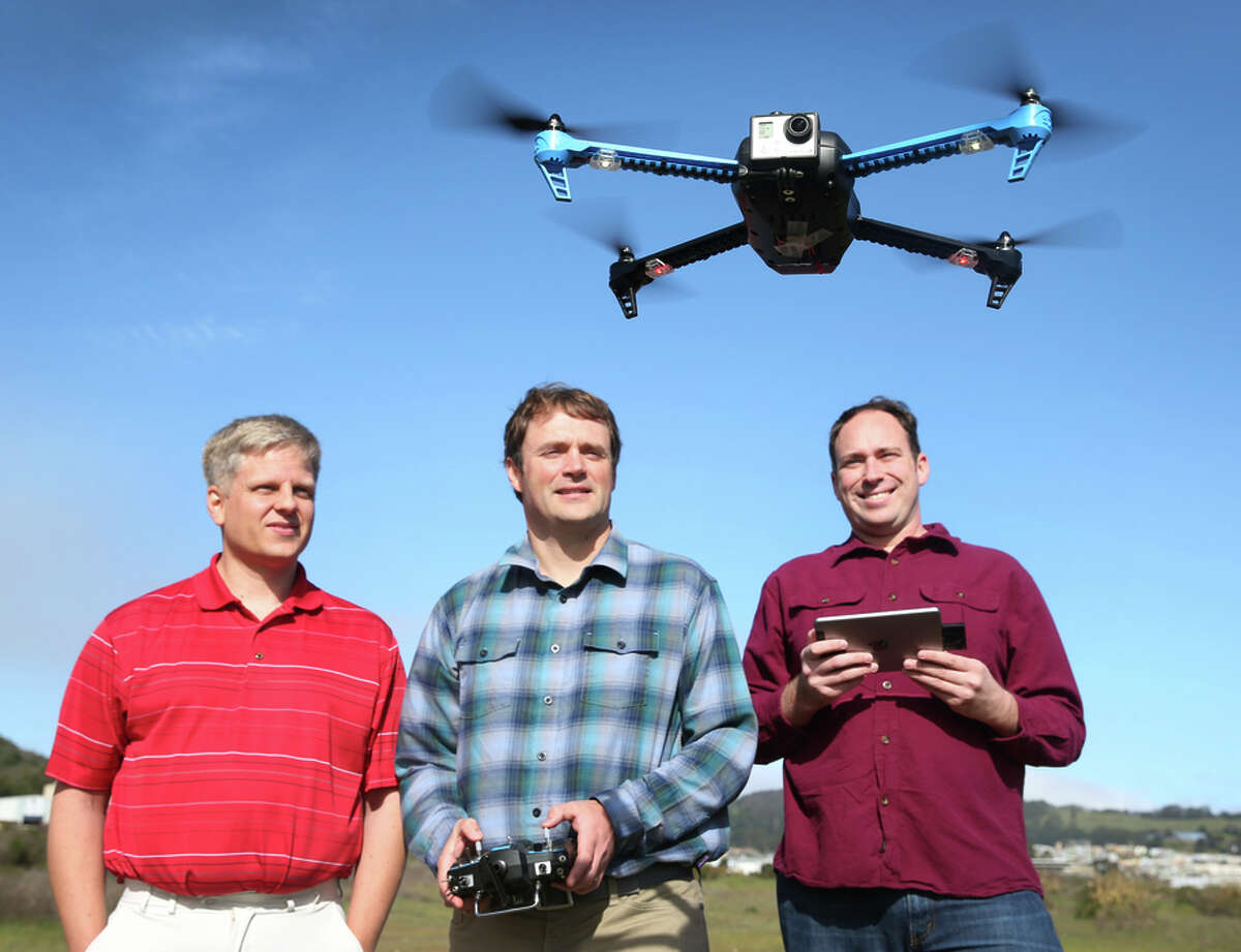 Dave Leskowicz (left), Bryan Galusha and Andy Brown, developers of the iDroneLink system, pilot a drone in Brisbane.