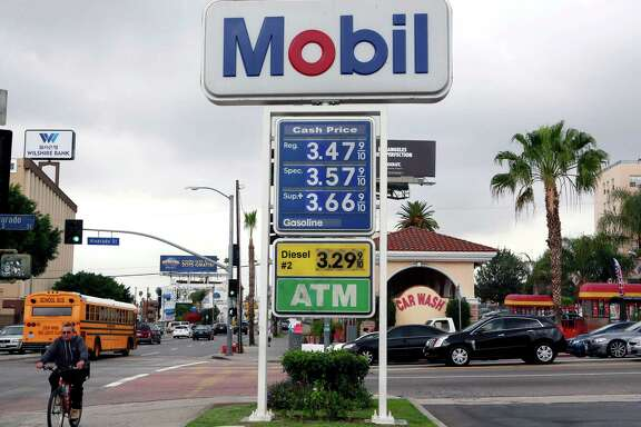 A cyclist rides by a sign at a gas station in Los Angeles posting the latest gas prices on Friday, Feb. 27, 2015. Gas prices in California soared overnight as a result of a combination of supply-and-demand factors worsened by the shutdown of two refineries that produce a combined 16 percent of the state's gasoline. (AP Photo/Nick Ut)