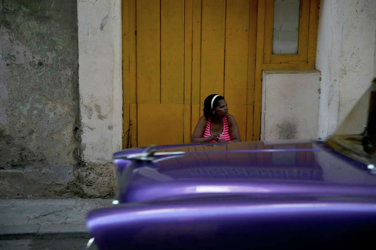 A woman sits in front of a building on Friday in Havana, Cuba. This week in Washington D.C., the second round of diplomatic talks between U.S. and Cuban officials is an effort to restore full diplomatic relations and move toward opening trade.