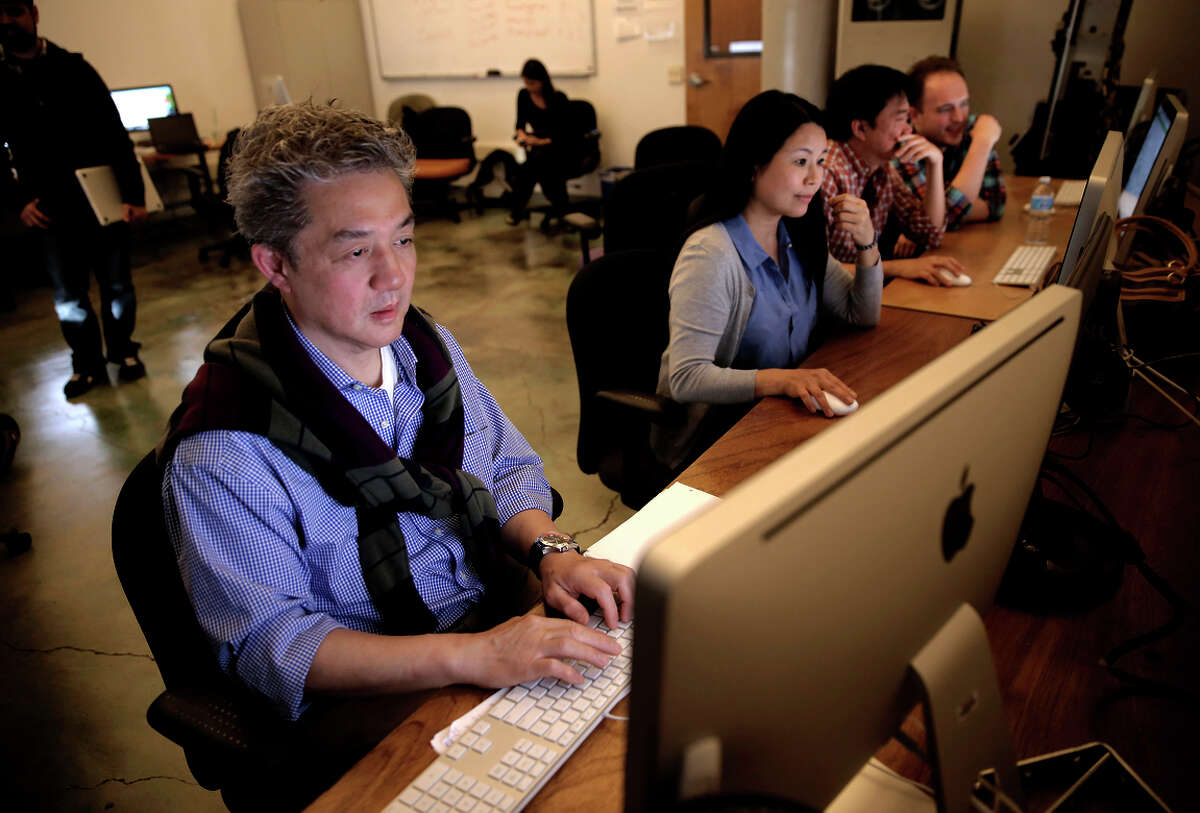 Joe McCarron (far right) of Zendesk guides students, from left, Winston Wu, Miao Ye and Kit Te through the Zendesk Basics Community Certification Training Program, during an open house in San Francisco.