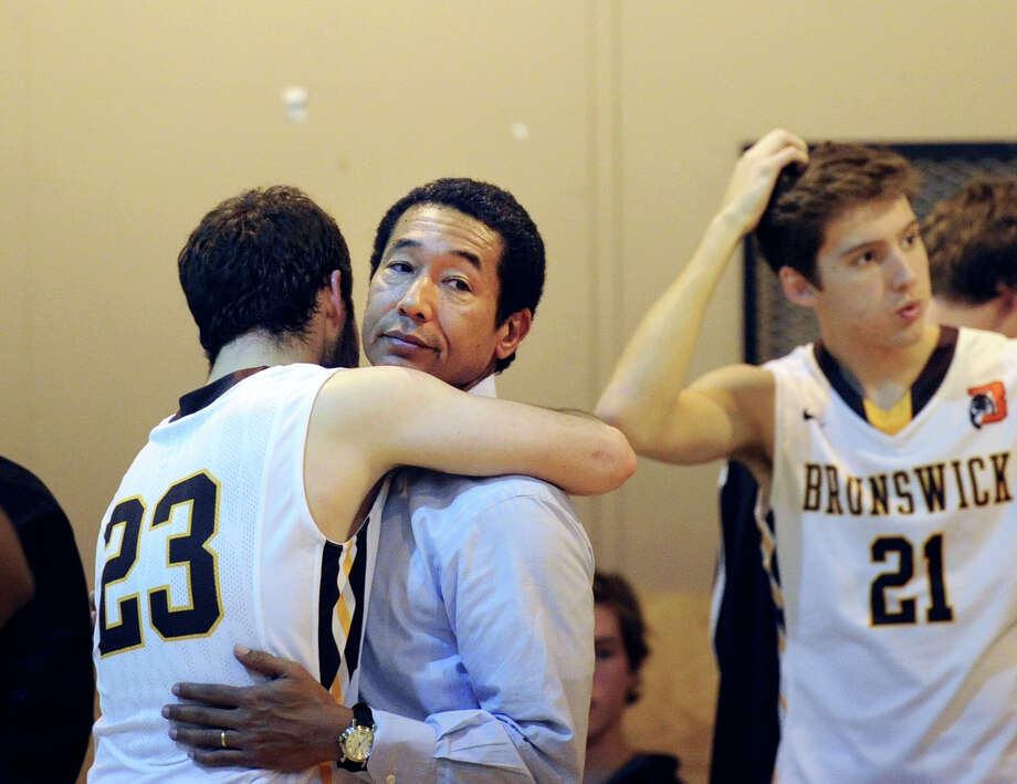 At left, Brunswick's Billy O'Malley (#23) hugs his coach Robert Taylor at the conclusion of the FAA boys high school basketball semifinal game that Brunswick School lost to Masters School by a score of 80-77 at Masters School in Dobbs Ferry, N.Y., Friday, Feb. 27, 2015. At right is O'Malley's Brunswick teammate, Patrick Ryan (#21). Photo: Bob Luckey / Greenwich Time