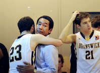 At left, Brunswick's Billy O'Malley (#23) hugs his coach Robert Taylor at the conclusion of the FAA boys high school basketball semifinal game that Brunswick School lost to Masters School by a score of 80-77 at Masters School in Dobbs Ferry, N.Y., Friday, Feb. 27, 2015. At right is O'Malley's Brunswick teammate, Patrick Ryan (#21).