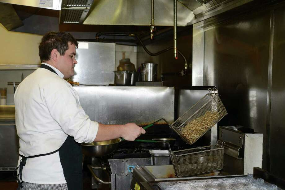 Chef Mark Thompson prepares frites, or  french fries, at Tribeca 212 on Wednesday, Feb. 25, 2015. Photo: Billy Calzada, Staff / San Antonio Express-News / San Antonio Express-News