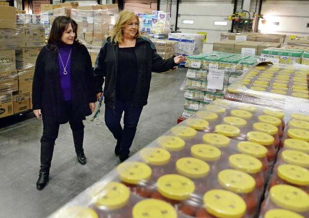 Regional Food Bank of Northeastern New York's  Joanne Dwyer, left, and Price Chopper's Pamela Cerrone, look over the 1,300 cases (17,780 pounds) of food that Price Chopper is donating to the Regional Food Bank of Northeastern New York at the Price Chopper distribution center Friday Feb. 27, 2015 in Schenectady, NY.  (John Carl D'Annibale / Times Union) Photo: John Carl D'Annibale / 00030804A