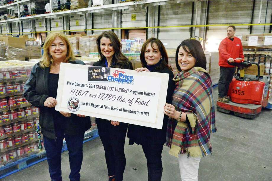 Price Chopper's Pamela Cerrone, left, and Ashley Lonardelli present 1,300 CASES (17,780 pounds) of food to the Regional Food Bank of Northeastern New York's  Joanne Dwyer and Caitlyn Krug as part of its annual Check Out Hunger program during a ceremony at the Price Chopper distribution center Friday Feb. 27, 2015 in Schenectady, NY.  (John Carl D'Annibale / Times Union) Photo: John Carl D'Annibale / 00030804A