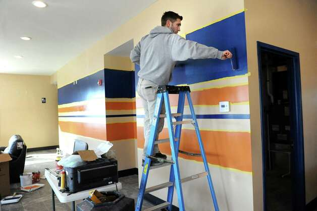 Employee Dede Lleshi paints the wall accents at Afrim Nezaj's newest indoor soccer complex on Friday, Feb. 27, 2015, at Afrim's Sports in Bethlehem, N.Y. (Cindy Schultz / Times Union) Photo: Cindy Schultz / 00030773A