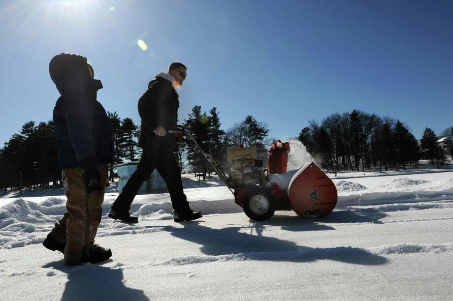 Garth Osier of Schenectady clears snow on Iroquois Lake in Central Park with his son Dominick, 3, on Friday, Feb. 27, 2015 in Schenectady, N.Y. Osier was making several ice rinks for skaters and hockey players. (Lori Van Buren / Times Union) Photo: Lori Van Buren / 00030812A