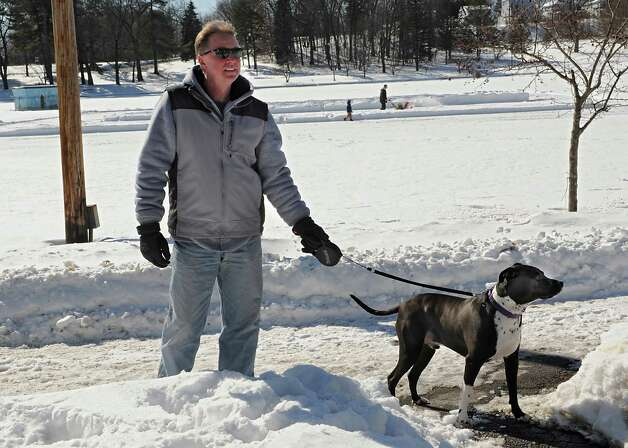 Tom Billsborrow stops to talk to a reporter about ice skating in Central Park while walking his dog Ottis on Friday, Feb. 27, 2015 in Schenectady, N.Y. Garth Osier of Schenectady clears snow on Iroquois Lake with his son Dominick, 3, in the background. Osier was making several ice rinks for skaters and hockey players. (Lori Van Buren / Times Union) Photo: Lori Van Buren / 00030812A