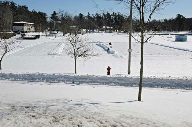 Garth Osier of Schenectady clears snow on Iroquois Lake in Central Park with his son Dominick, 3, on Friday, Feb. 27, 2015 in Schenectady, N.Y. Osier was making several ice rinks for skater