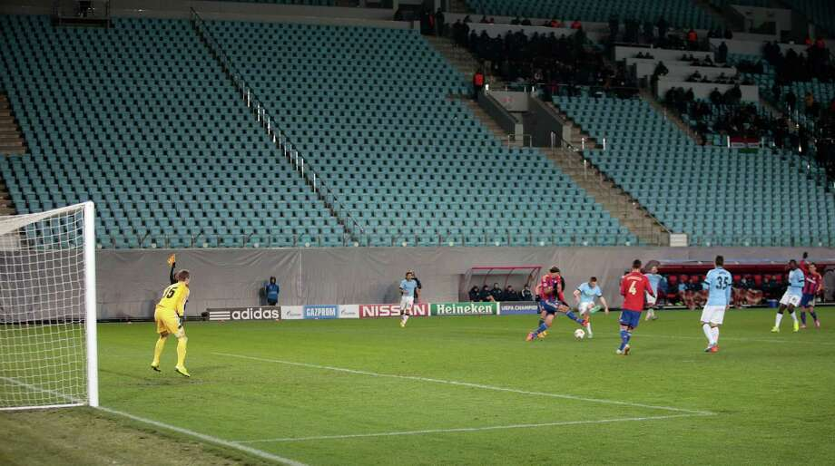 In this Tuesday, Oct. 21, 2014, file photo, Manchester City players and CSKA players play in front of empty stands during the Champions League Group E soccer match between CSKA Moscow and Manchester City at Arena Khimki stadium in Moscow. CSKA have to play 3 matches behind closed doors after as punishment for the bad behaviour of their fans last season. Russian football is plagued by a racist and far-right extremist fan culture that threatens the safety of visitors to the 2018 World Cup, a dossier provided to The Associated Press revealed on Friday. (AP Photo/Ivan Sekretarev, File) Photo: Ivan Sekretarev, STF / AP