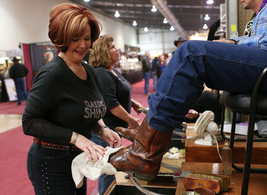 Denise Pullen shines a customer's boots at the Expo Hall of the San Antonio Stock Show and Rodeo, Wednesday, February 25, 2015. Pullen is the owner of the Plano-base company that operates chairs in something like 40 locations that includes malls, airports and rodeos across the nation. Photo: JERRY LARA, Staff / San Antonio Express-News / © 2015 San Antonio Express-News