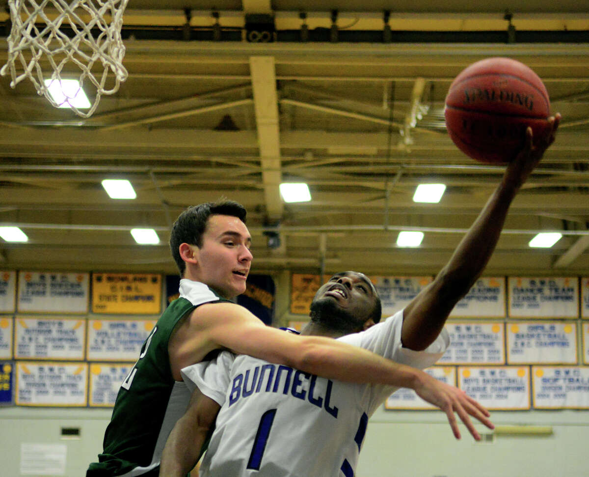 Bunnell's Ryan Pittman gets fouled by New Milford's Nick Peixoto as he attempts to score, during boys basketball action in Stratford, Conn. on Friday Feb. 27, 2015.