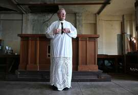 Jesuit priest Fr. Bernie Bush dons an alb, part of which was crocheted by former prisoner Lawrence Trumblay, while visiting the old cell house chapel on Alcatraz in San Francisco, Calif. on Wednesday, Feb. 25, 2015. Father Bush regularly visited the former federal penitentiary for several years while he was studying in the priesthood in the 1960's and became close friends with convicted bank robber Lawrence Trumblay.