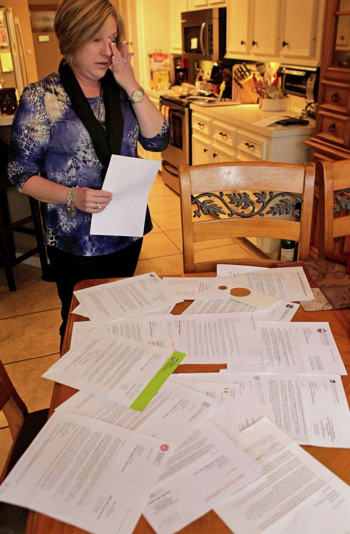 Traci Hobson wipes away tears as she lays out more than a dozen college letters sent to her 16-year-old son Grant Hobson, who died Feb. 7 after taking synthetic LSD.