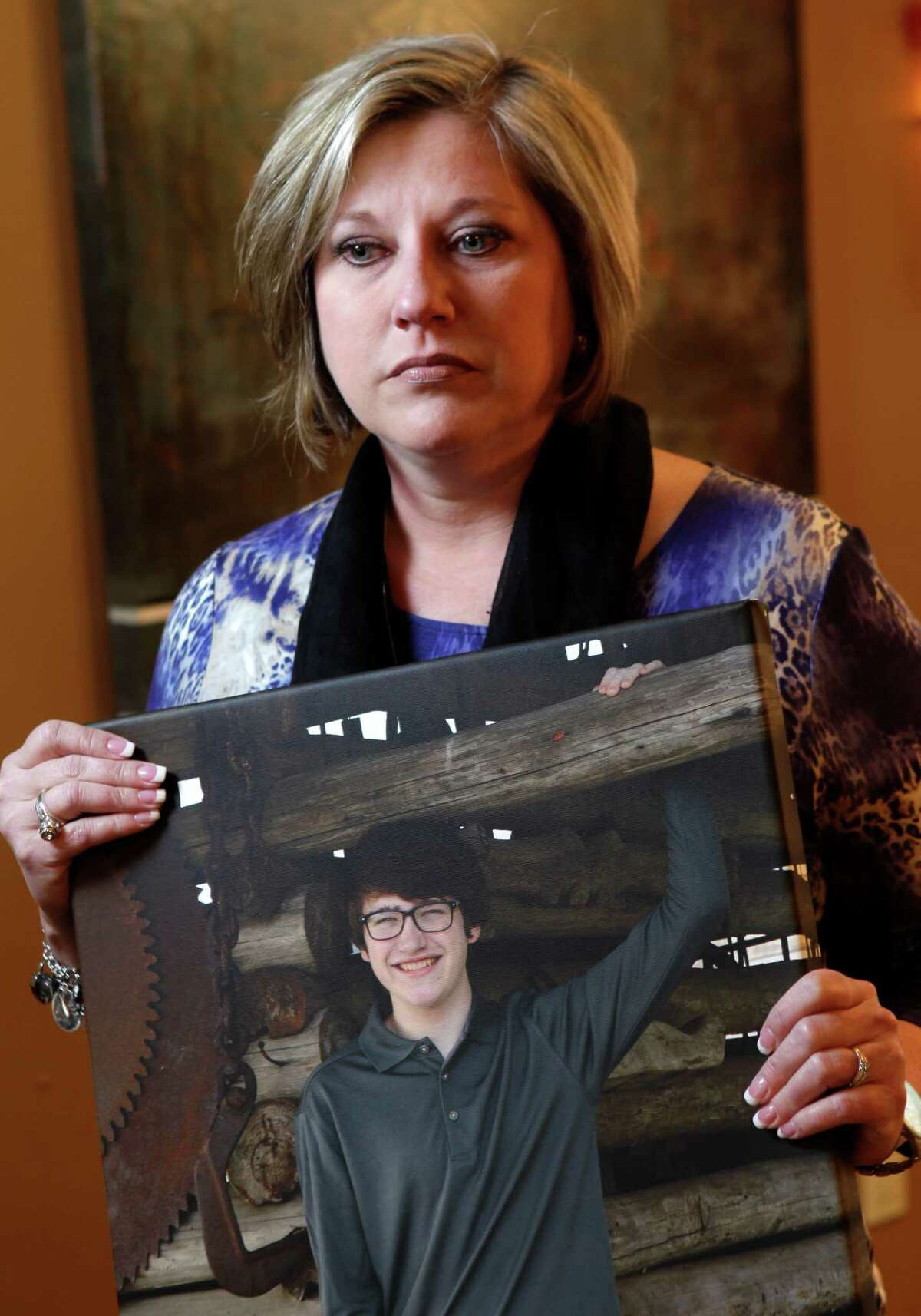 Traci Hobson, poses with a photo taken in December of her 16-year-old son Grant Hobson, who died Feb. 7 after taking synthetic LSD.