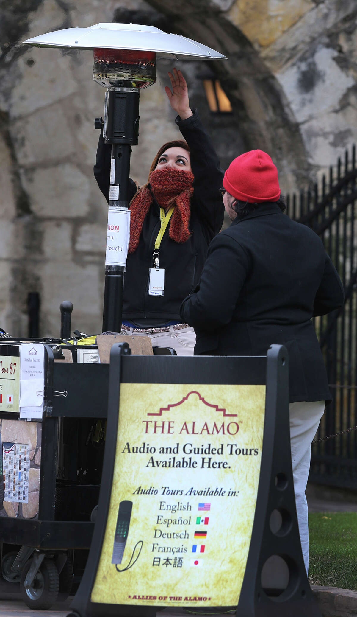 Idalis Salinas warms her hands under a portable heater in front of the Alamo.