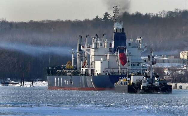 A stripe of smoke hangs over the Hudson River as the freighter Cano gets underway with a powered barge following close behind in the Port of Albany Friday morning Feb. 27, 2015 in Albany, N.Y.      (Skip Dickstein/Times Union) Photo: SKIP DICKSTEIN / 00030798A