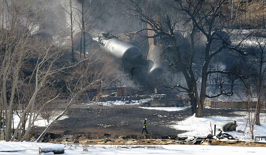 FILE - In this Feb. 17, 2015 file photo, crew members walk near the scene of a train derailment near Mount Carbon, W.Va. A CSX train carrying more than 100 tankers of crude oil derailed in a snowstorm, sending a fireball into the sky. Fiery wrecks this month of trains hauling crude oil have intensified pressure on the Obama administration to approve tougher standards for railroads and tank cars despite industry complaints that it could cost billions and slow freight deliveries. (AP Photo/Chris Tilley, File) ORG XMIT: WX103 Photo: Chris Tilley / FR171192 AP