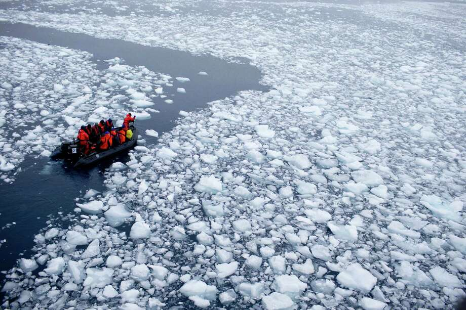 In this Jan. 22, 2015 photo, a zodiac carrying a team of international scientists heads to Chile's station Bernardo O'Higgins, Antarctica. Water is eating away at the Antarctic ice, melting it where it hits the oceans. As the ice sheets slowly thaw, water pours into the sea, 130 billion tons of ice (118 billion metric tons) per year for the past decade, according to NASA satellite calculations. (AP Photo/Natacha Pisarenko) ORG XMIT: NAT501 Photo: Natacha Pisarenko / AP