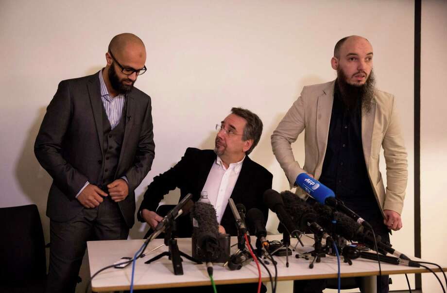 "CAGE research director, Asim Qureshi, left, and spokesman Cerie Bullivant, right, take their seats next to political activist John Rees at the start of a press conference held by the CAGE human rights charity in London, Thursday, Feb. 26, 2015.  A British-accented militant who has appeared in beheading videos released by the Islamic State group in Syria bears ""striking similarities"" to a man who grew up in London, a Muslim lobbying group said Thursday. Mohammed Emwazi has been identified by news organizations as the masked militant more commonly known as ""Jihadi John."" London-based CAGE, which works with Muslims in conflict with British intelligence services, said Thursday its research director, Asim Qureshi, saw strong similarities, but because of the hood worn by the militant, ""there was no way he could be 100 percent certain."" (AP Photo/Matt Dunham) ORG XMIT: LMD101 Photo: Matt Dunham / AP"