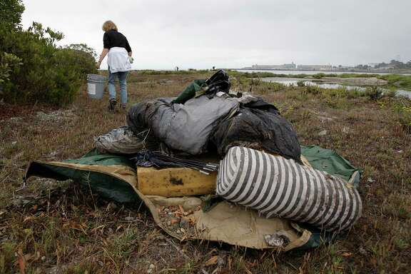 A volunteer search the marshes of Heron's Head Park in the Bayview district of San Francisco, during a beach cleanup day.