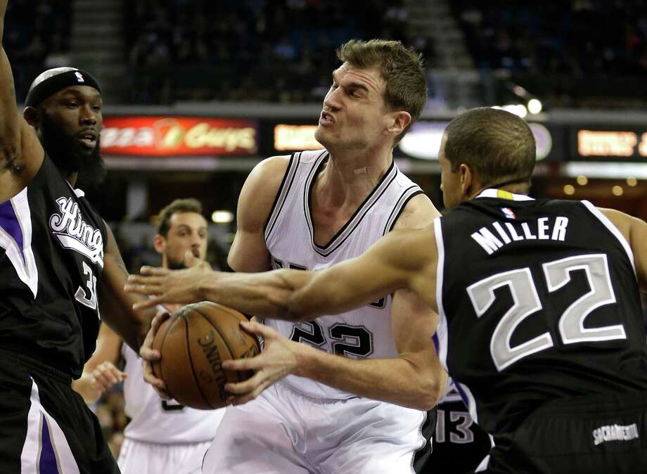 San Antonio Spurs center Tiago Splitter, center, of Brazil,  is fouled by Sacramento Kings guard Andre Miller, right, as Kings forward Reggie Evans looks on during the first quarter of an NBA basketball game in Sacramento, Calif., Friday, Feb. 27, 2015.(AP Photo/Rich Pedroncelli) Photo: Rich Pedroncelli, STF / Associated Press / AP