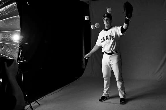 San Francisco Giants' Buster Posey tosses a glove full of baseballs in the air during Photo Day at Spring Training at Scottsdale Stadium in Scottsdale, Arizona, on Friday, February 27, 2015.