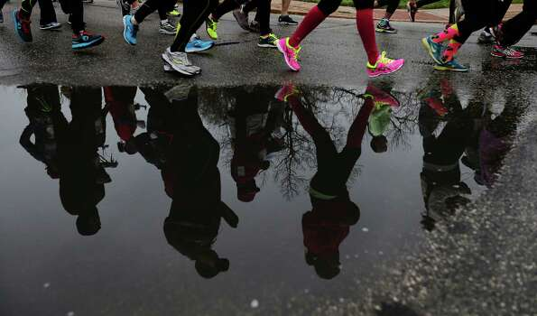Runners stride past a pool of rain water at the start of the Missions Marathon Half run starting at Mission Concepcion on Saturday, Feb. 28, 2015. Despite near freezing temperatures and early drizzle, hundreds of runners were not dissuaded from taking part in the inaugural running event from which all proceeds went to the Las Misiones Permanent Fund which helps restore the four Spanish missions located in San Antonio: Mission Espada, Missoin San Jose, Mission San Juan and Mission Concepcion. Photo: Kin Man Hui, San Antonio Express-News / ©2015 San Antonio Express-News