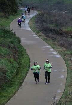 Miriam Flores (right) and Veronica Ibarra join other runners making their way along a curved path of the Mission Reach while participating in the Missions Marathon Half run starting at Mission Concepcion on Saturday, Feb. 28, 2015. Despite near freezing temperatures and early drizzle, hundreds of runners were not dissuaded from taking part in the inaugural running event from which all proceeds went to the Las Misiones Permanent Fund which helps restore the four Spanish missions located in San Antonio: Mission Espada, Missoin San Jose, Mission San Juan and Mission Concepcion. Photo: Kin Man Hui, San Antonio Express-News / ©2015 San Antonio Express-News